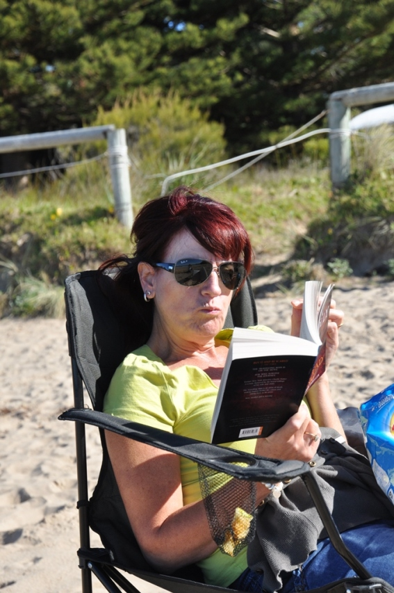 Gail reading a book on the beach.