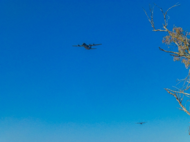 A couple of military transport plane fly overhead.